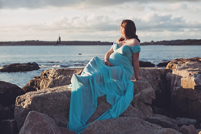 Maternity photo session at Brenton Point State Park in Rhode Island. She is wearing a teal maternity dress and is looking outward to the ocean while sitting on the rocks